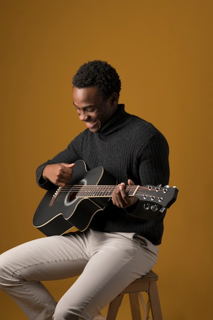 Schwarzer junge spielt gitarre Kostenlose Fotos