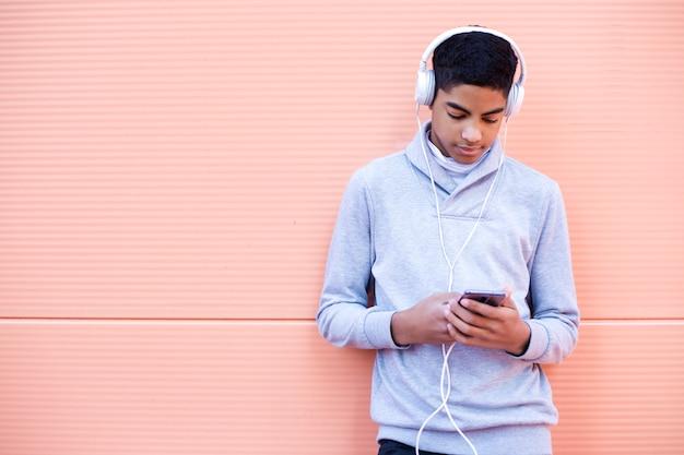 Schwarzer junger mann hört musik an seinem handy bei der stellung auf der straße. afroamerikanerjugendlicher in den kopfhörern unter verwendung eines smartphone. Premium Fotos