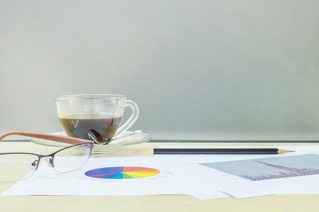 Schwarzer kaffee der nahaufnahme mit arbeitspapier auf hölzernem schreibtisch Premium Fotos