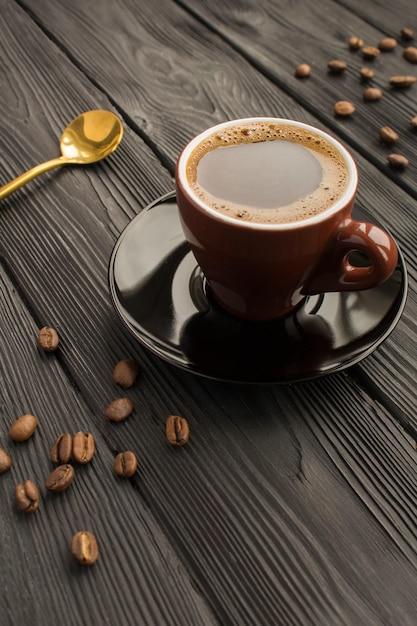 Schwarzer kaffee in der braunen tasse auf dem schwarzen Premium Fotos