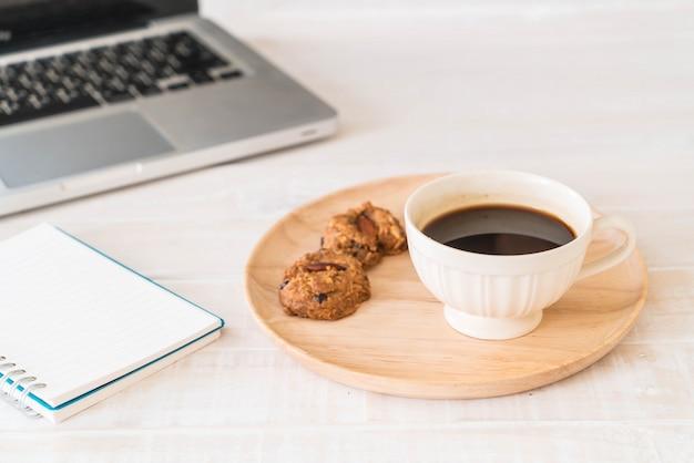 Schwarzer kaffee und kekse mit laptop und notizbuch Kostenlose Fotos