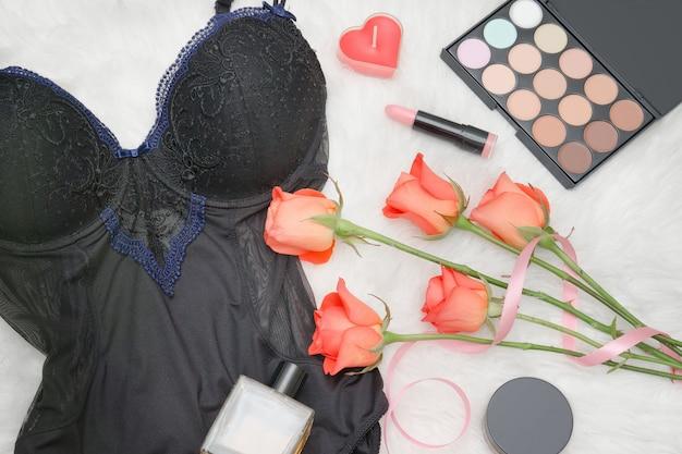 Schwarzer körper, orange rosen, lippenstift, parfüm und lidschatten. modisches konzept Premium Fotos