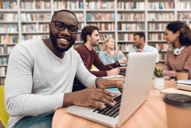 Schwarzer mann auf laptop in der schulbibliothek. Premium Fotos