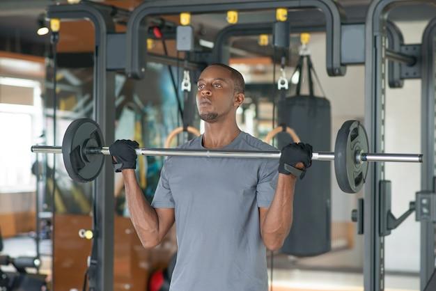 Schwarzer mann, der barbell in der turnhalle steht und anhebt Kostenlose Fotos