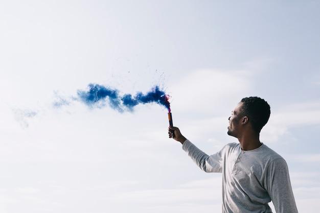 Schwarzer mann, der farbige rauchbomben anhebt Kostenlose Fotos