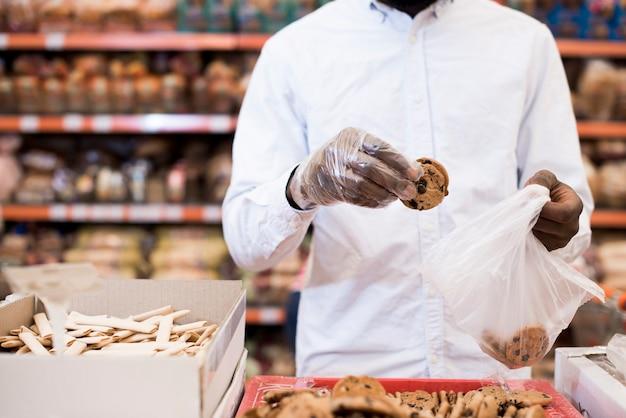 Schwarzer mann, der plätzchen in plastiktasche in lebensmittelgeschäft einsetzt Kostenlose Fotos