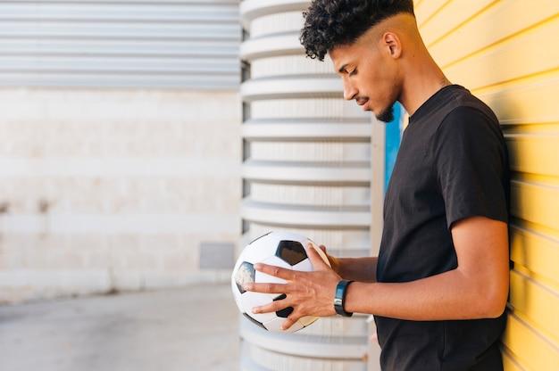 Schwarzer mann, der unten ball in den händen betrachtet Kostenlose Fotos