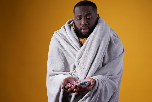 Schwarzer mann hat erkältung und hält pillen in händen. Premium Fotos
