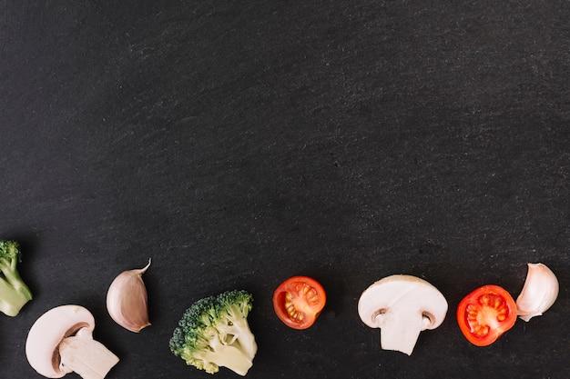 Schwarzer oberflächenhintergrund mit pilz; brokkoli; knoblauchzehe und kirschtomaten Kostenlose Fotos