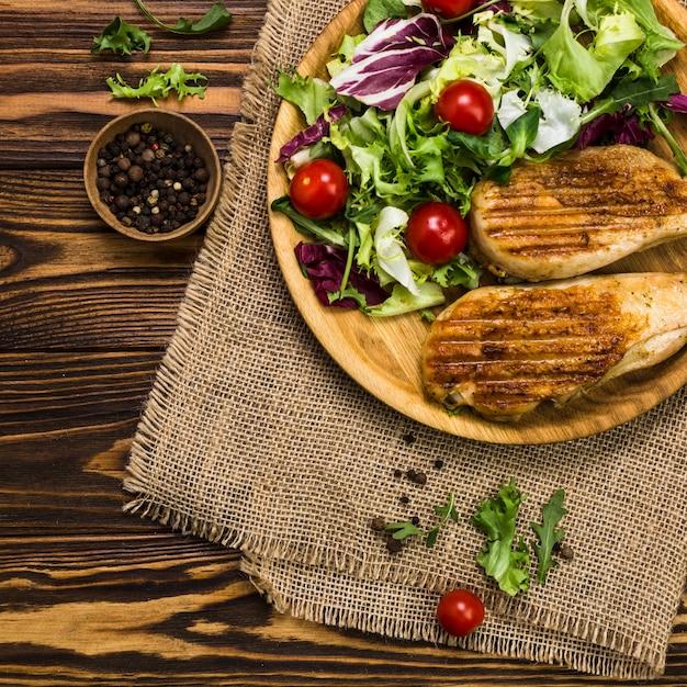 Schwarzer pfeffer in der nähe von salat und brathähnchen Kostenlose Fotos