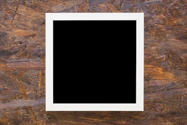 Schwarzer rahmen der weißen grenze auf hölzernem hintergrund Premium Fotos