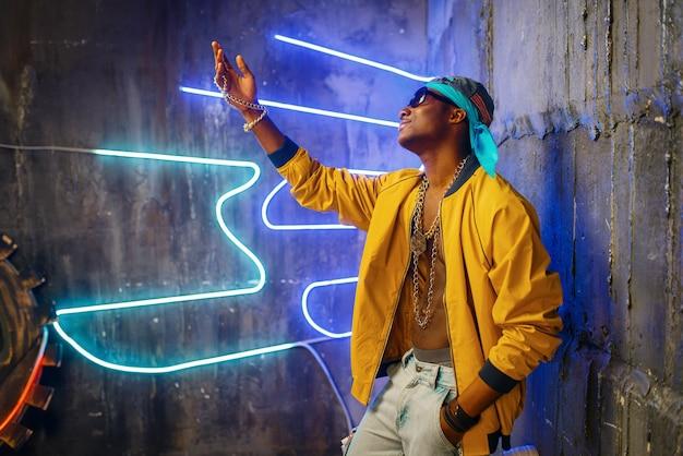 Schwarzer rapper im unterführungs-neonlicht Premium Fotos