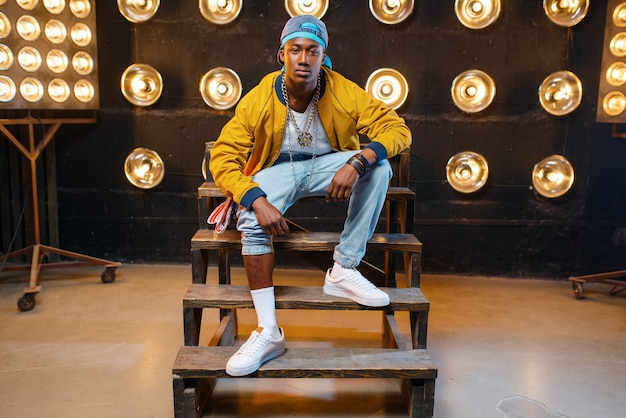 Schwarzer rapper in der mütze sitzt auf den stufen, sänger auf der bühne mit scheinwerfern an der wand. rap-darsteller vor ort mit lichtern, underground-musik, urbanem stil Premium Fotos