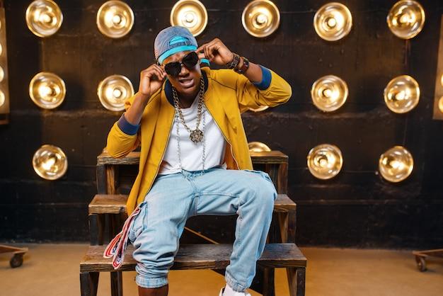 Schwarzer rapper in mütze und sonnenbrille sitzt auf den stufen, sänger auf der bühne mit scheinwerfern an der wand. rap-darsteller vor ort mit lichtern, underground-musik, urbanem stil Premium Fotos