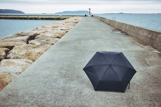 Schwarzer regenschirm auf der fußwegweise. nahe dem meer. Premium Fotos
