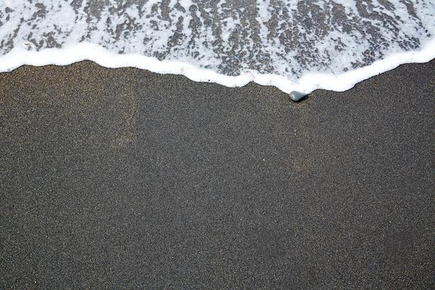 Schwarzer sandstrand mit wellenschaum fuerteventura Premium Fotos