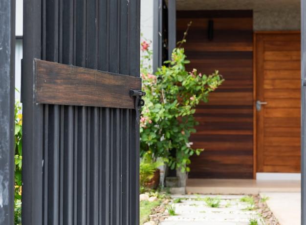 Schwarzer stell tür-zauneingang zum haus mit gehweg des betonblocks und der weißen steine Premium Fotos