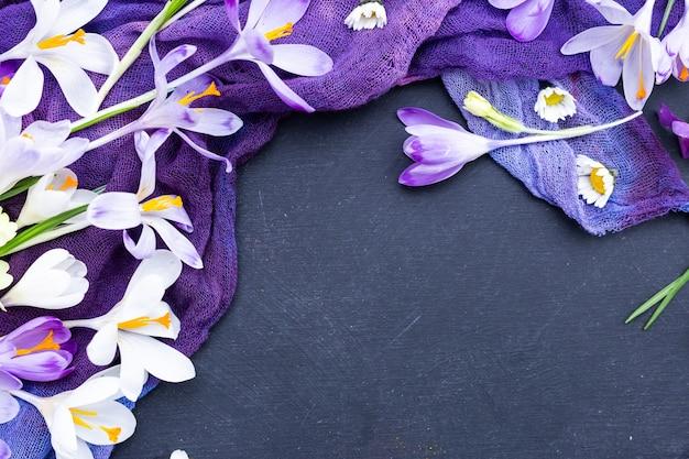 Schwarzer strukturierter hintergrund mit lila gefärbtem stoff und frühlingsblumen Kostenlose Fotos