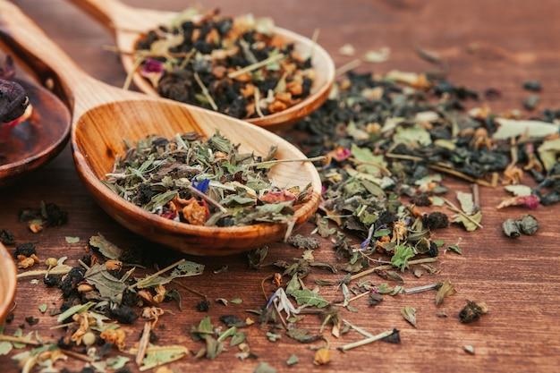 Schwarzer tee mit kräutern in den hölzernen löffeln auf einem hölzernen brett Premium Fotos