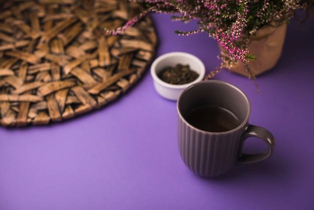Schwarzer tee mit kräutern und untersetzer auf purpurrotem hintergrund Kostenlose Fotos