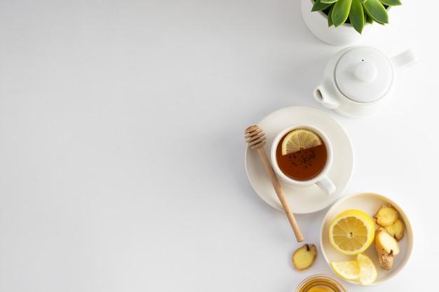 Schwarzer tee mit zitrone und honig auf einem weiß. heiße teeschale lokalisiert, draufsichtebenenlage. flach liegen. herbst-, herbst- oder wintergetränk. copyspace. Premium Fotos