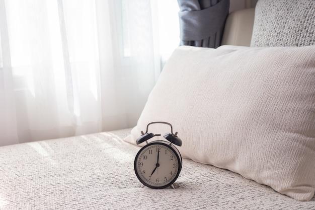 Schwarzer wecker auf weißem bett im wohnzimmer. Premium Fotos