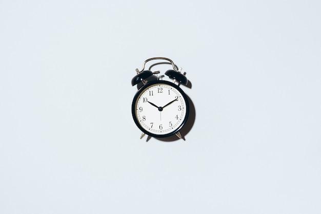 Schwarzer wecker mit hartem schatten auf grauem hintergrund. Premium Fotos