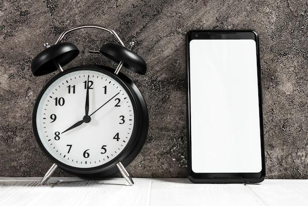 Schwarzer wecker und smartphone mit weißem leerem bildschirm auf schreibtisch gegen konkrete schwarze wand Kostenlose Fotos