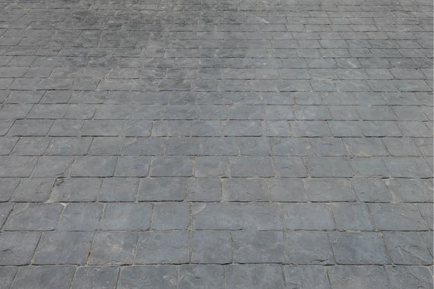 Schwarzer ziegelsteinoberflächenboden der nahaufnahme am bahnbeschaffenheitshintergrund Premium Fotos