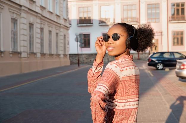 Schwarzes afroamerikanisches mädchen hat einen spaziergang in der abendstadt und hört musik in den kopfhörern. mädchen in der sonnenbrille im sommer lächelt und schaut auf sonnenuntergang. Premium Fotos