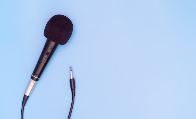 Schwarzes dynamisches mikrofon auf blauem kopienraum Premium Fotos