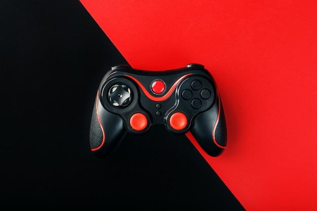 Schwarzes gamepad auf einer schwarzen roten oberfläche Premium Fotos