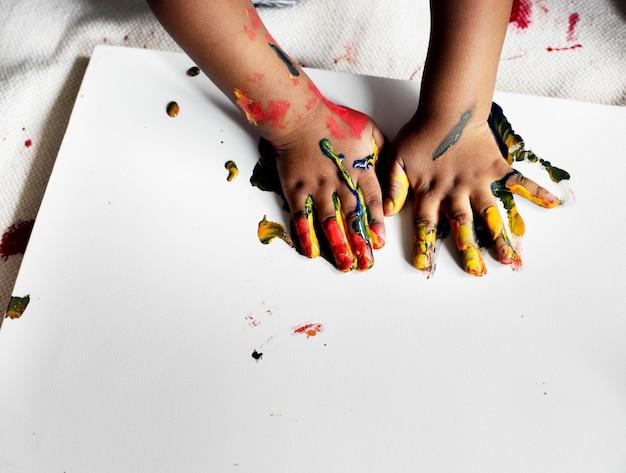 Schwarzes kind, das seine malerei genießt Kostenlose Fotos