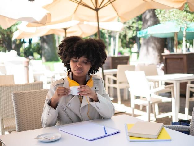 Schwarzes mädchen, das einen kaffee während der arbeit trank, saß an einem tisch auf einer bar, draußen Premium Fotos