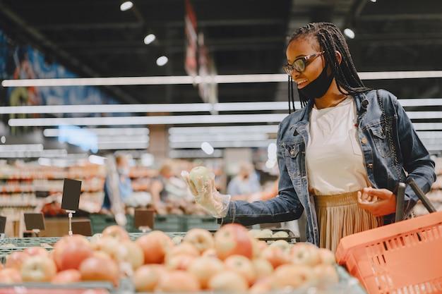 Schwarzes mädchen in einer maske kaufen ein essen Kostenlose Fotos