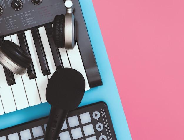 Schwarzes mikrofon und kopfhörer auf blauem und rosa hintergrund der tischplatteansicht für kopienraum Premium Fotos