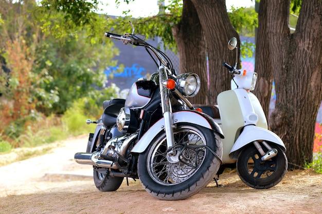 Schwarzes motorrad der weinlese, das nahe weißem motorrad in den strahlen des sonnenlichts steht. seitenansicht Premium Fotos