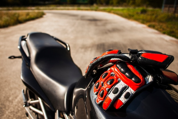 Schwarzes motorrad mit dem reiten von roten handschuhen Kostenlose Fotos