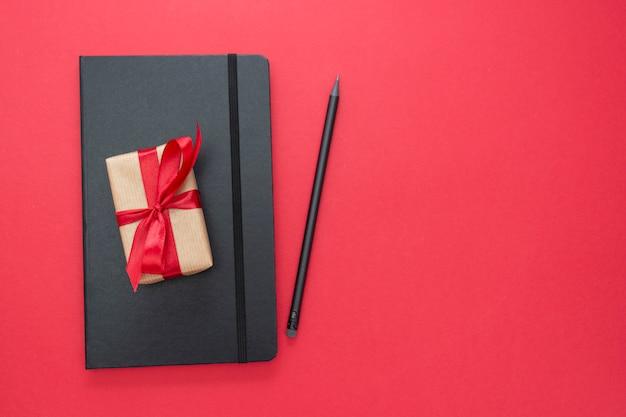 Schwarzes notizbuch auf rotem hintergrund mit einer geschenkbox. valentinstag-konzept. Premium Fotos