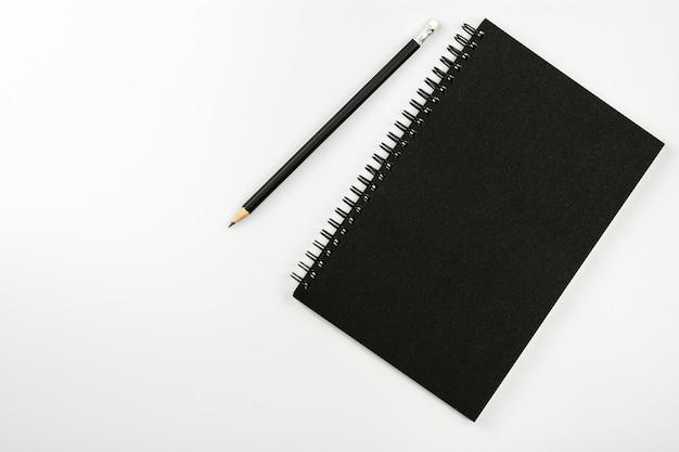 Schwarzes notizbuch und ein bleistift auf weißem schreibtischhintergrund mit kopienraum Premium Fotos