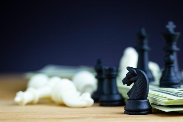 Schwarzes schach steht auf dollarbanknoten und holztische mit weißem schach fällt. Premium Fotos