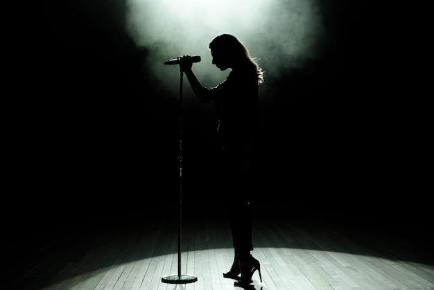 Schwarzes schattenbild der sängerin mit weißen scheinwerfern im hintergrund Premium Fotos