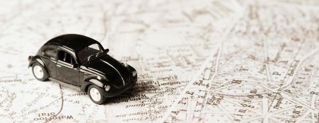 Schwarzes spielzeugauto mit hohem winkel auf karten Kostenlose Fotos