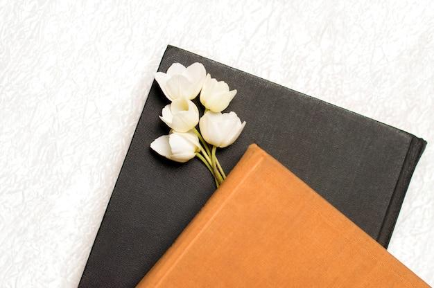 Schwarzes und braunes buch mit blumen auf einem weiß Premium Fotos