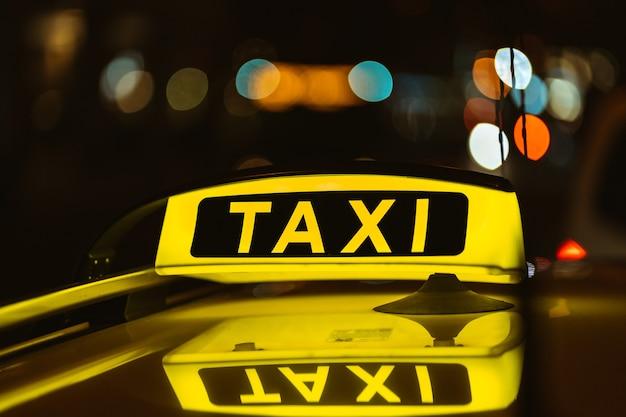 Schwarzes und gelbes zeichen des taxis in der nacht auf einem auto platziert Kostenlose Fotos