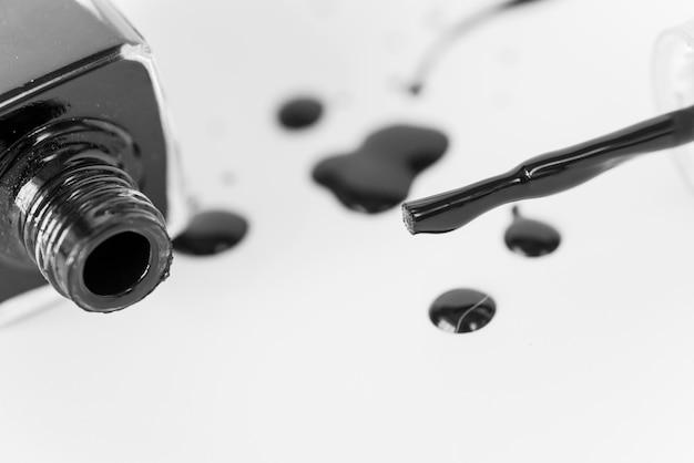 Schwarzes verschüttete nagellackflasche auf weißem hintergrund Kostenlose Fotos