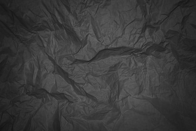 Schwarzes zerknittertes blatt papier mit vignettierung Premium Fotos