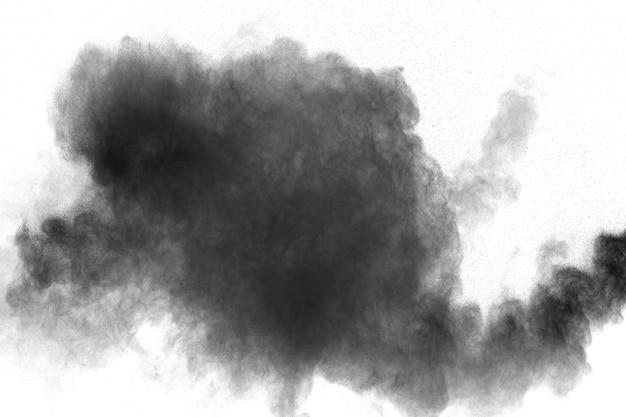 Schwarzpulverexplosion gegen weißen hintergrund. schwarze staubpartikel spritzen. Premium Fotos