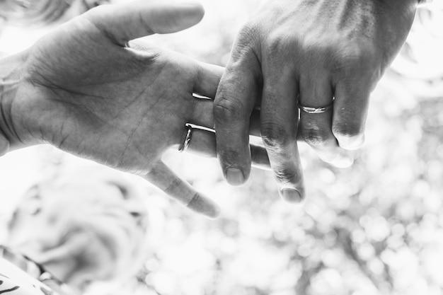 Schwarzweiss-bild der hände der jungvermählten, die sich zart halten Kostenlose Fotos
