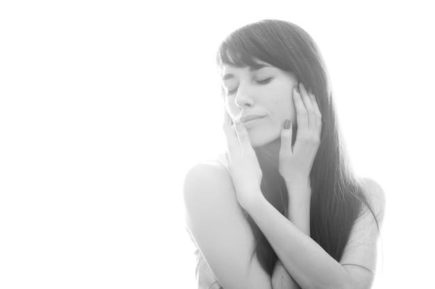 Schwarzweiss-foto eines mädchens auf einem weißen hintergrund in einer leichten haltung Premium Fotos